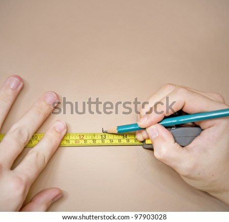 measuring with tape measure and marking wall with pencil - stock photo