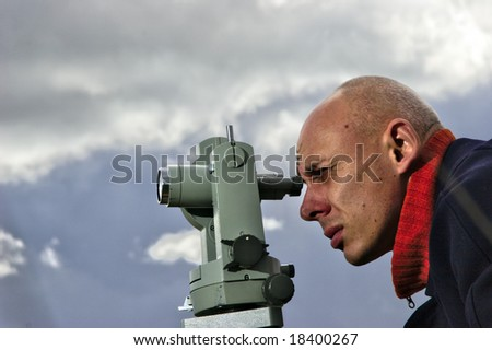 Measuring with theodolite - spring land surveying - stock photo