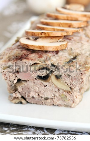 Meat and mushroom terrine garnish with raw mushrooms - stock photo