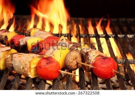 Meat And Vegetable Kebabs On The Hot BBQ Grill Closeup. Flaming  Charcoal Grill In The Background. Snack For Outdoor Summer Barbeque Party. - stock photo
