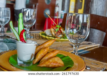 meat and vegetable samosas served in a small restaurant, meal time - stock photo