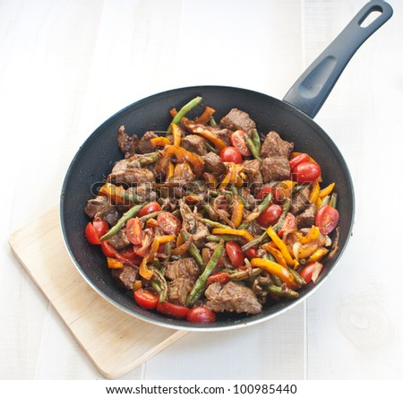 Meat and vegetables in frying pan - stock photo