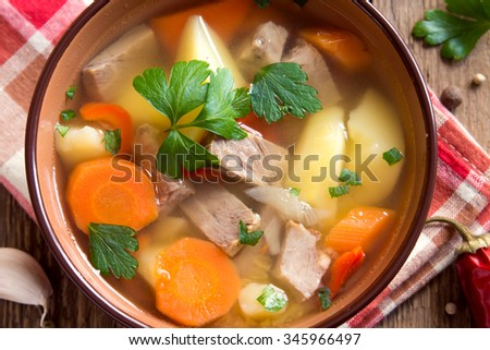 Meat and vegetables soup with parsley in bowl over rustic wooden background close up