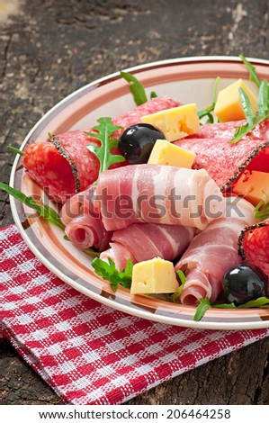 Meat appetizer on a plate on old wooden background