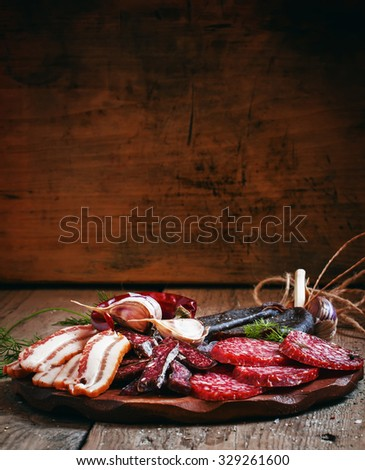 Meat appetizer platter with bacon, smoked sausage and salami on a wooden cutting board, selective focus - stock photo