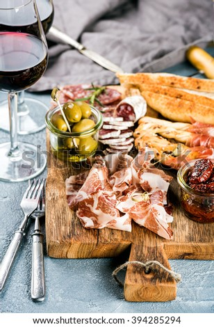 Meat appetizer selection. Salami, prosciutto, bread sticks, baguette, olives and sun-dried tomatoes, two glasses of red wine over grey concrete textured backdrop, selective focus - stock photo