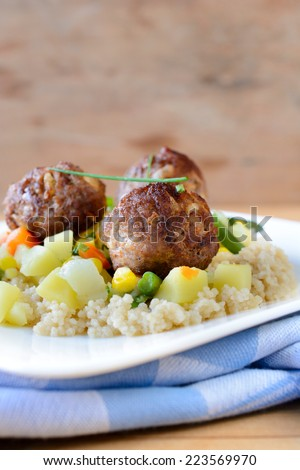 Meat balls with couscous and vegetables in the plate,selective focus and blank space above  - stock photo