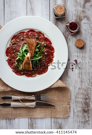 Meat carpaccio of beef on wood table
