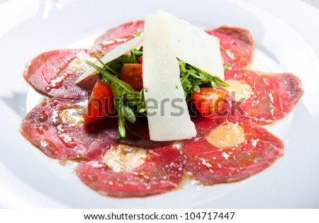 Meat carpaccio with parmesan cheese, tomatoes and herbs