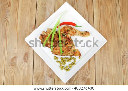 meat : chicken quarters garnished with green sweet peas and red hot pepper on white plate over wooden table - stock photo