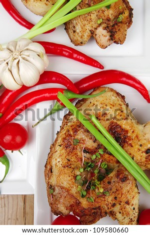 meat : chicken quarters garnished with green sweet peas and red hot peppers on white plates over wooden table - stock photo