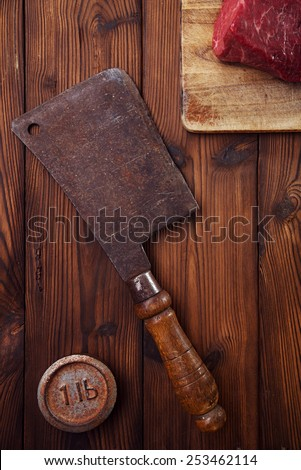 meat cleaver butcher knife with raw beef meat fillet  on wooden  table  and 1lb iron weight - stock photo