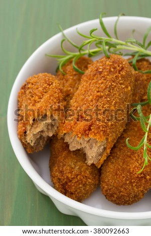 meat croquettes in white dish on green wooden background