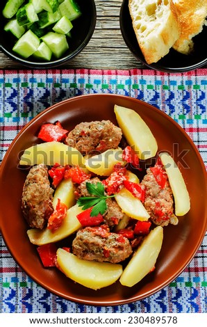 meat cutlets baked with potatoes, tomatoes and red pepper. keftesi. a Turkish dish. tinting. selective focus on parsley - stock photo