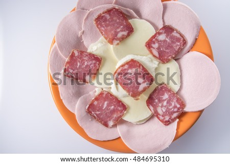 Meat cuts with mozzarella on orange plate on a light background