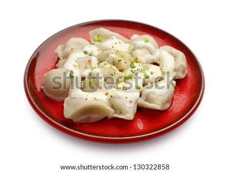 Meat dumplings on a red plate on white - stock photo