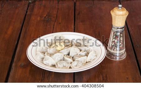 Meat dumplings - russian pelmeni on wooden background.  - stock photo