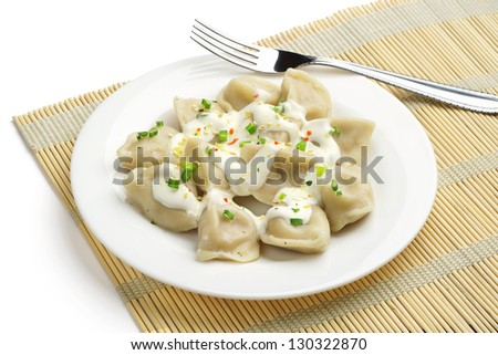 Meat dumplings with sour cream on a plate - stock photo