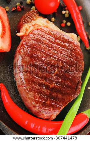 meat entree : grilled beef steak served with hot cayenne peppers red tomato green chives on metal pan isolated over white background - stock photo