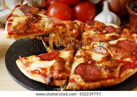 Meat feast Barbecue pizza with a topping of pepperoni, sausage, salami and chicken wings