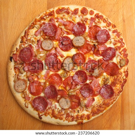 Meat feast pizza with pepperoni, ham and spicy sausage topping. - stock photo