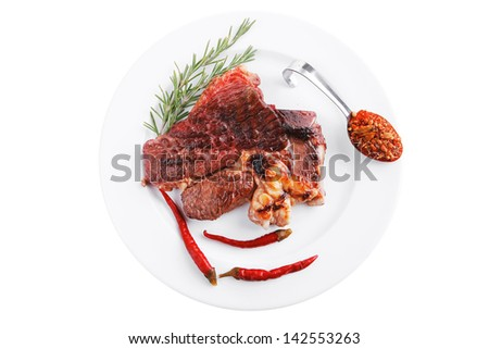 meat food : grilled beef steak served on white plate with red thin chili pepper and spices isolated over white background