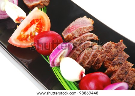 meat food : grilled fat meat served on black plate with vegetables on spit isolated on white background