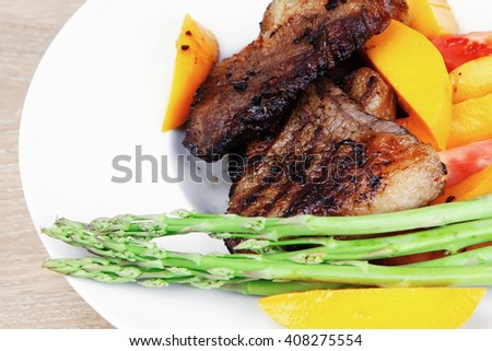 meat food : grilled red beef fillet with mango tomatoes and asparagus , served on white dish over wooden table - stock photo
