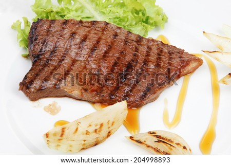 meat food : grilled steak on green lettuce salad , with roast onion, on dish isolated over white background