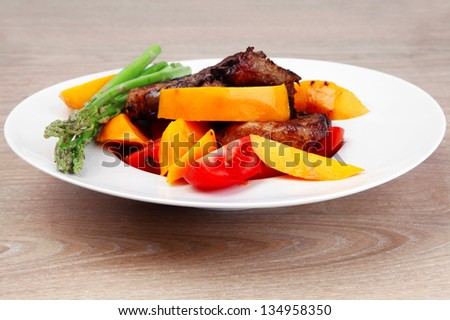 meat food : rare medium roast beef fillet with mango tomatoes and asparagus , served on white dish over wooden table