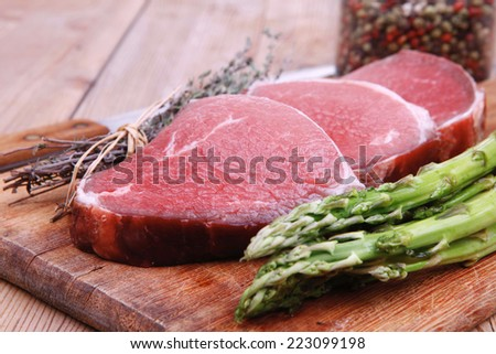 meat food : raw beef fillet on cutting board with asparagus and thyme bundle , with color peppercorn mix and red paprika powder mixed with dry spices ready to cooking - stock photo