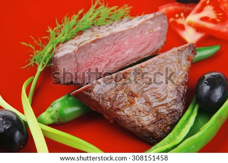 meat food : roast beef fillet mignon served on red plate with apples dill and tomatoes isolated over white background - stock photo