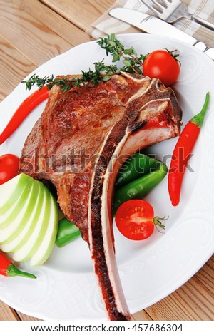 meat food : roast rib on white dish with thyme pepper and tomato on wooden table - stock photo