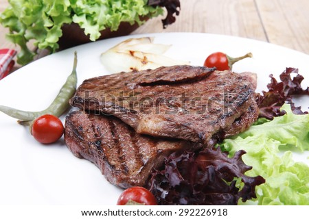 meat food : roast steak boneless with roast onion and red hot peppers, served on green lettuce salad on dish isolated over wooden table - stock photo