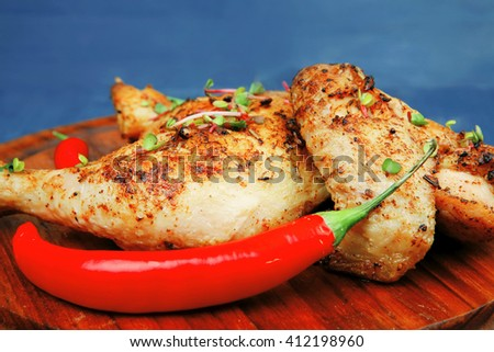meat food : roasted chicken legs garnished with green onion pens and peppers on wooden plate over blue wooden background - stock photo