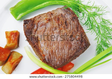 meat food : roasted fillet mignon on white plate with tomatoes apples and chili pepper isolated over white background - stock photo