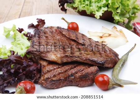 meat food : two grilled steak on green lettuce salad , with roast onion and red hot chili peppers , on dish over wooden table