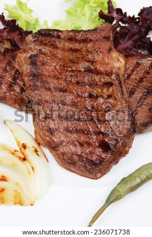 meat food : two grilled steak with chili and red peppers , green lettuce salad , on dish isolated over white background