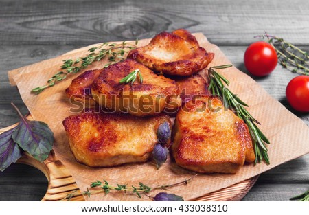 Meat fried pork steak baked, fresh green basil spices, thyme, rosemary, cherry tomatoes, gray dark wooden background in rustic style - stock photo