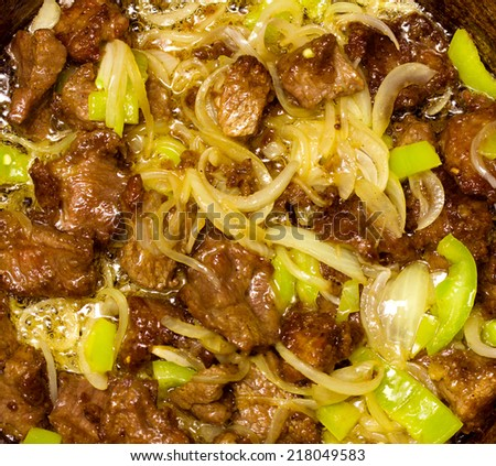 meat fried with onions and peppers, background