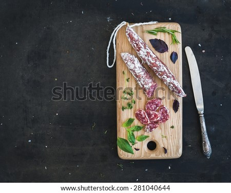 Meat gourmet snack. Salami, garlic and herbs on rustic wooden board over dark grunge backdrop, top view, copy space - stock photo