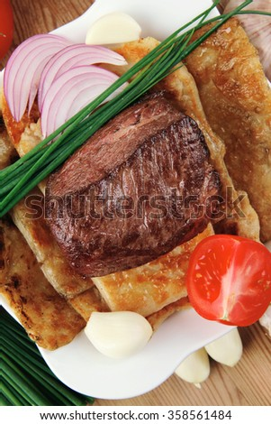 meat : grilled beef fillet mignon on bread with tomatoes salad on wooden table