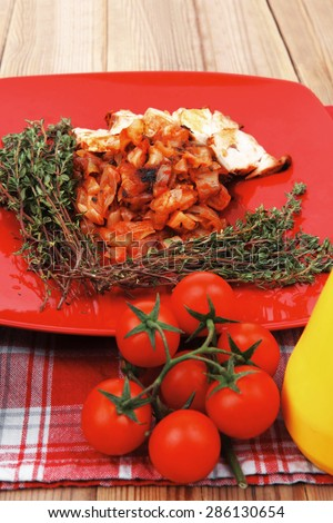 meat grilled chicken fillet with salad and tomatoes on red plate over wooden table with cutlery on lunch time - stock photo