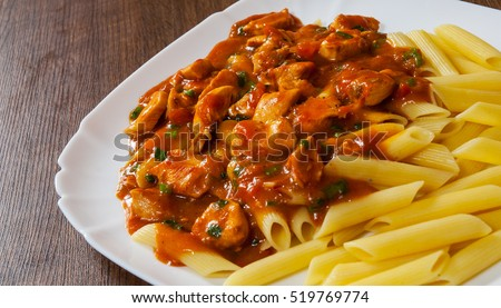 meat in tomato sauce with penne pasta in a plate on wooden table