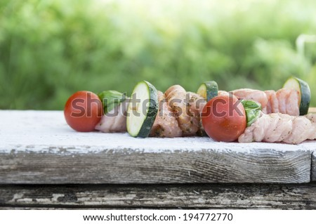 meat kebabs raw for grill on wooden table in garden