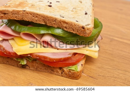 meat, lettuce , cheese and vegetables big sandwich on toasted whole wheat bread