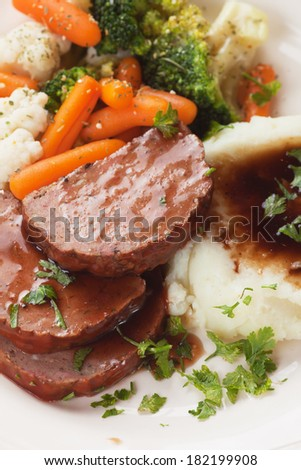 Meat loaf slices with mashed potato and cooked vegetables