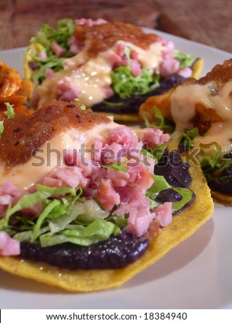 Meat mexican tacos and quesadillas with hot sauce, nachos, jalapenos, fried beans and cheese sauce, in a mexican restaurant - stock photo