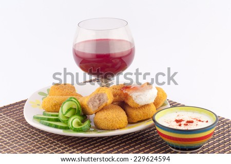 meat nuggets with sauce, cucumber and glass of red wine on a white background