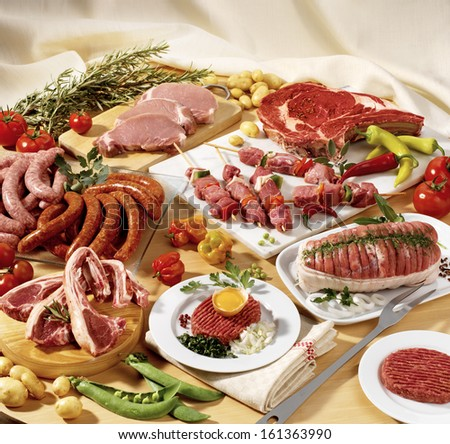 Meat on display -beef, veal, pork, lamb and sausage- with veggies and rosemary - stock photo